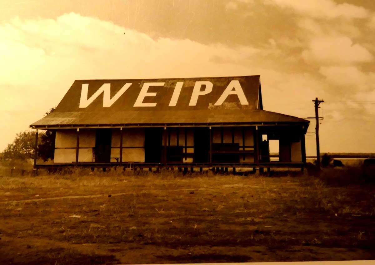 An old homestead building surrounded by dirt with Weipa written on the roof in large painted letters.
